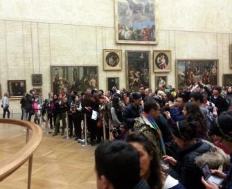 Mob of people photographing the Mona Lisa.