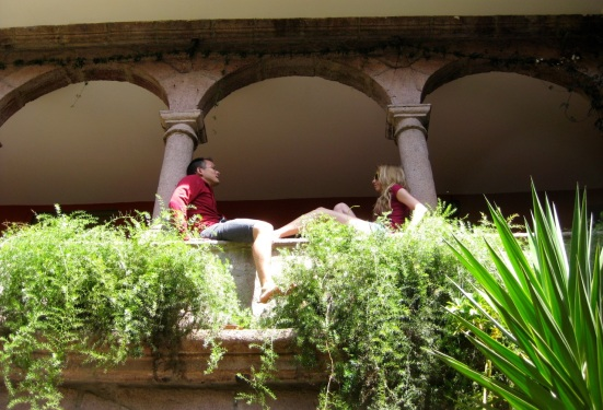A couple travelers chatting in the archway at Ecopackers. Cusco, Peru.