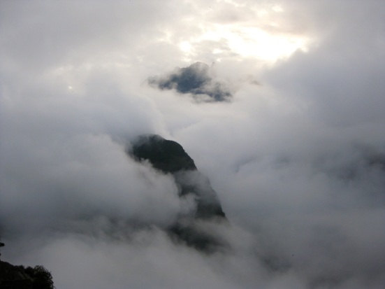 Early morning sun peeking through heavy fog at Machu Picchu.